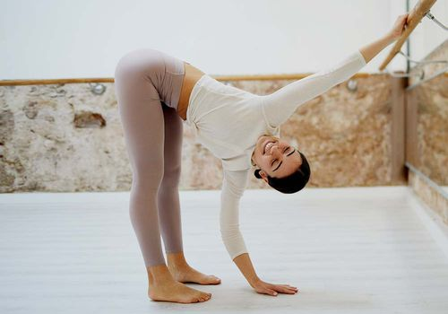 person stretching at the ballet barre