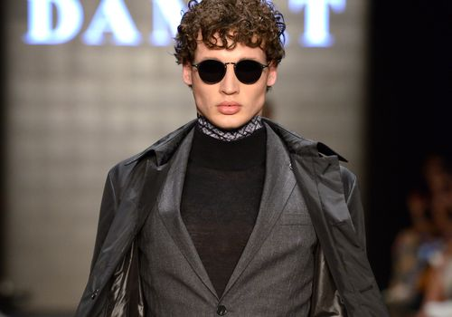 Man with curly hair on the runway