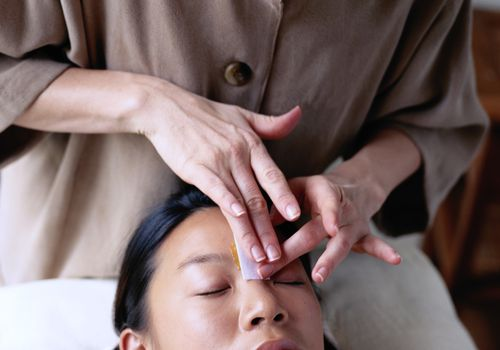 A young asian woman having her eyebrows waxed
