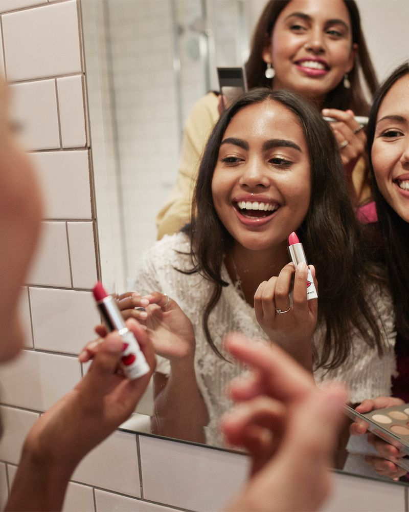 girls doing makeup together in bathroom mirror