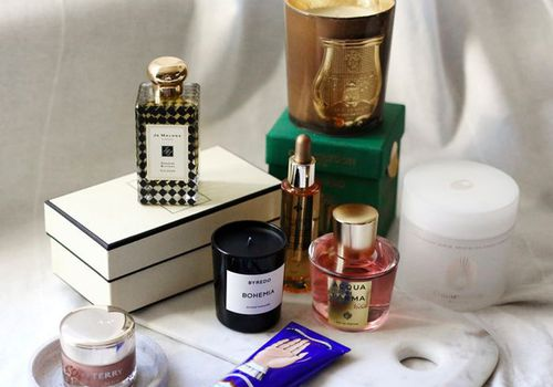 Perfumes, lotions, and candles sitting on a white surface