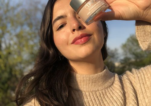 Young woman holding the Clinique Moisture Surge product