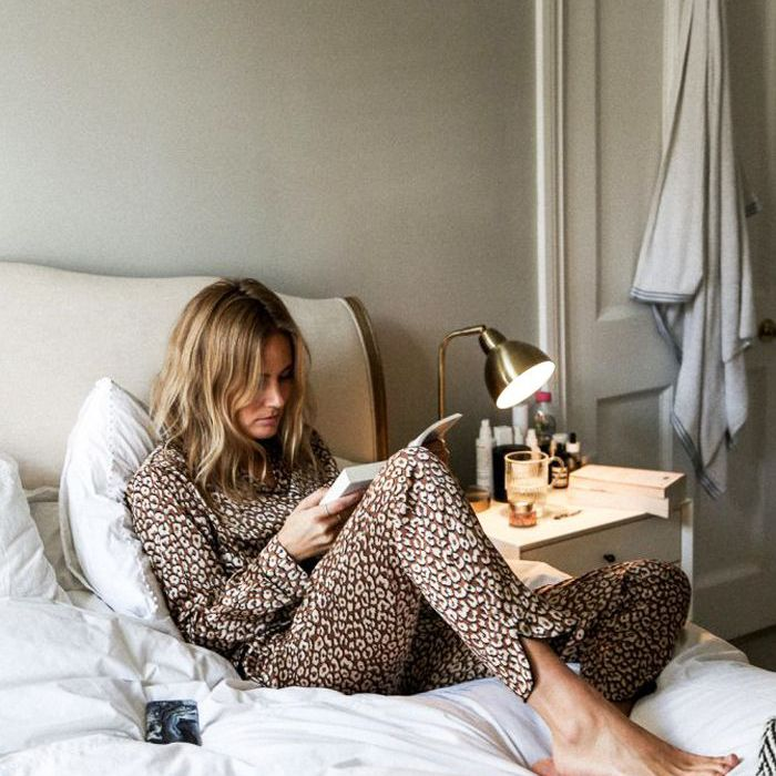 Influencer Lucy Williams reading a book in bed while wearing leopard pajamas
