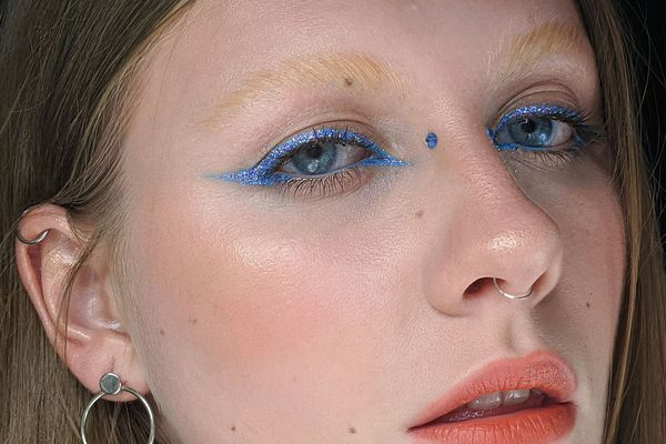 close-up of woman with bridge piercing and blue eyeliner