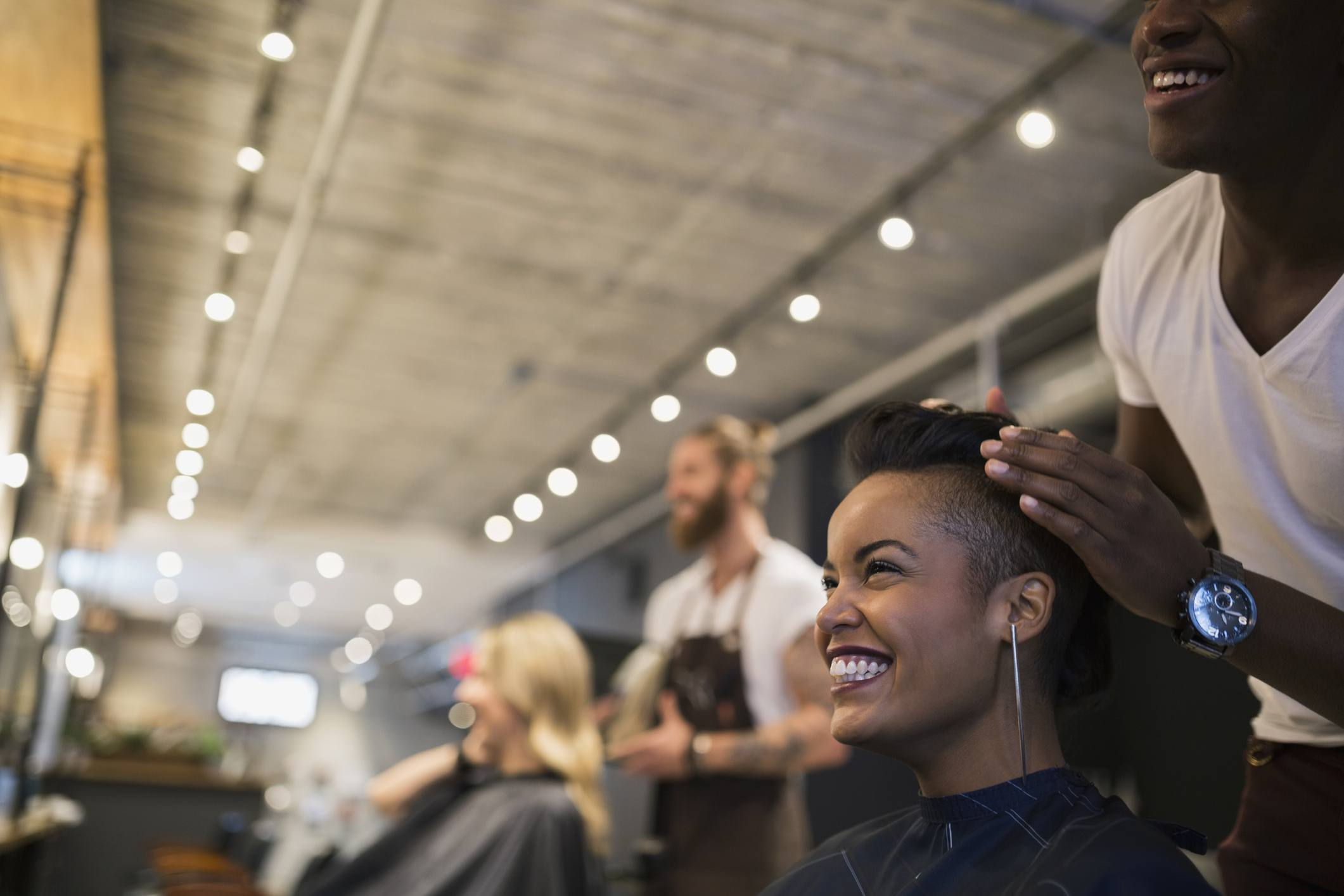 Black woman with a short mohawk smiling at her reflection in a salon mirror