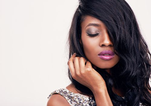 Black woman with metallic makeup and long, wavy hair