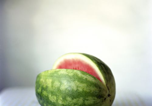 a watermelon on a table with a missing slice