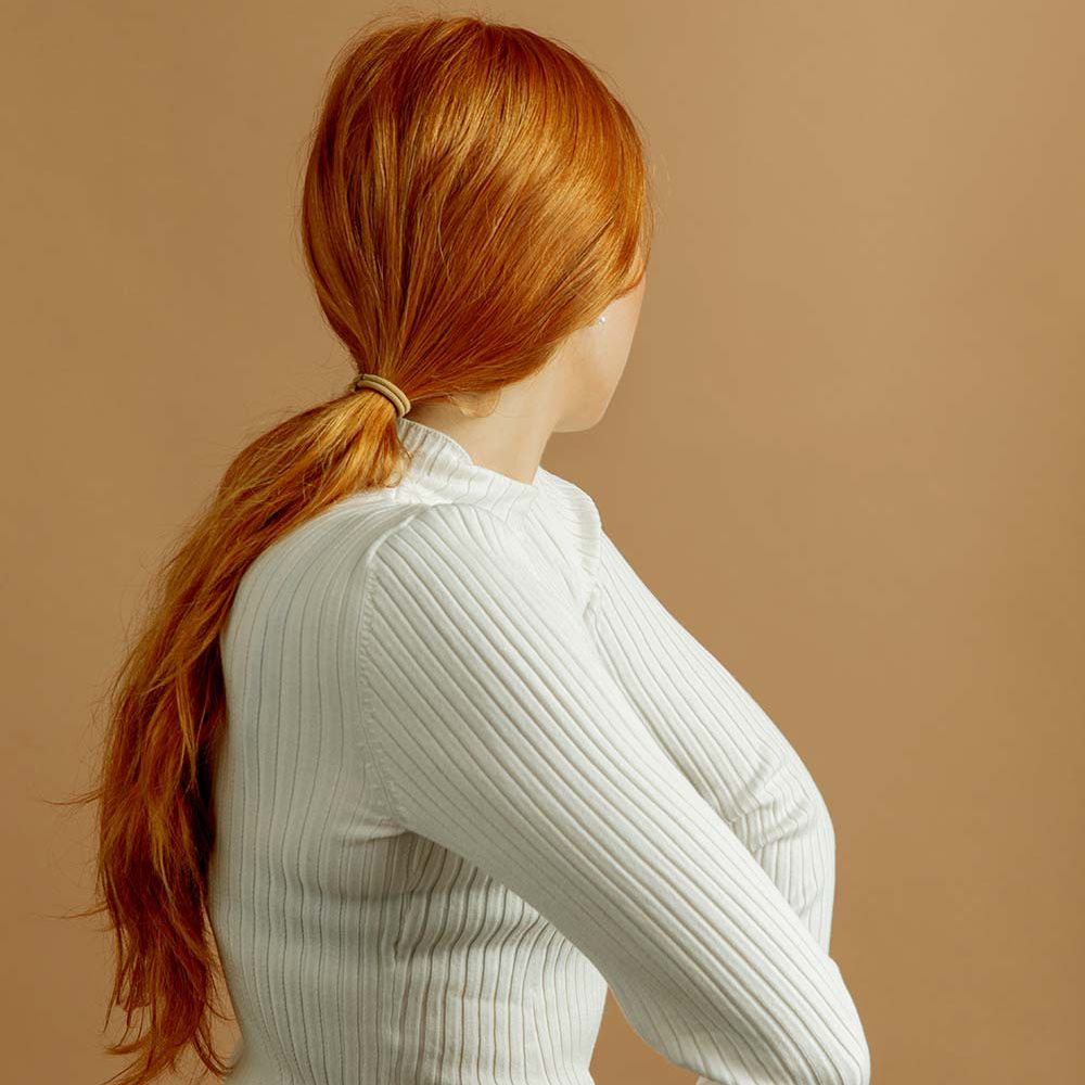 person with long red hair in ponytail from behind