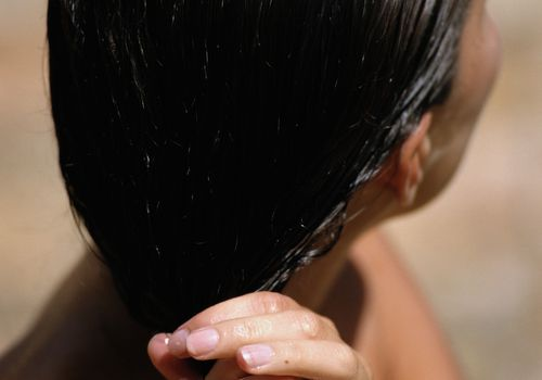 woman with damp hair ringing it out