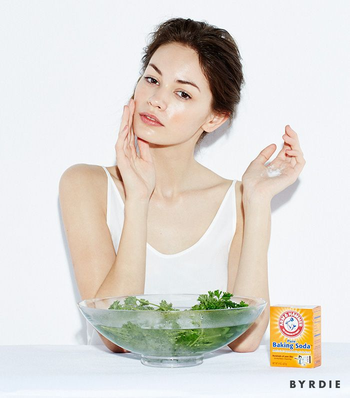 model touching face with bowl of herbs in water and baking soda