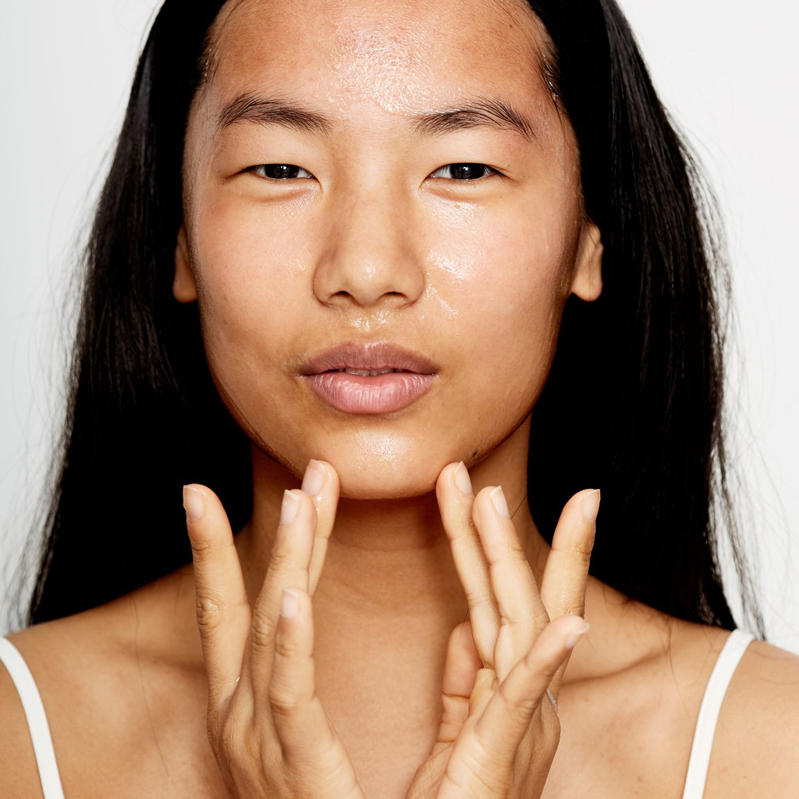 woman putting on oil makeup cream