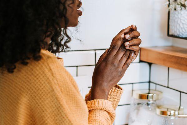 woman washing hands in tiled bathroom