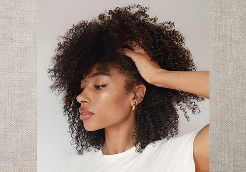 Woman holds her curly hair up