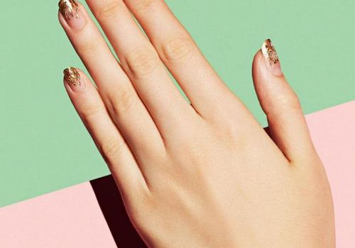hand with glitter nails against green and pink background