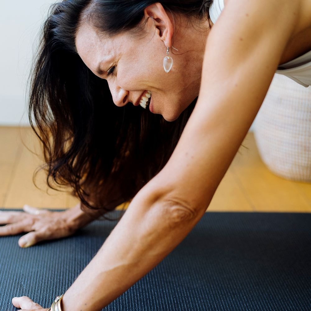 closeup of person laughing in down dog yoga pose