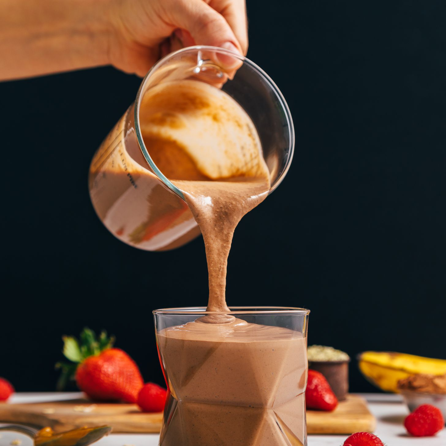 a chocolate protein shake being poured into a glass