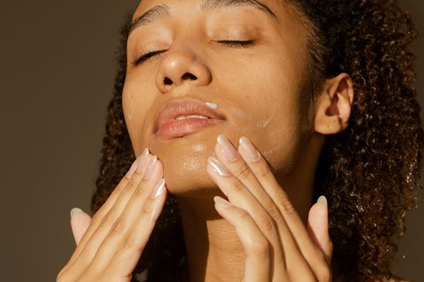 person applying moisturizer to face