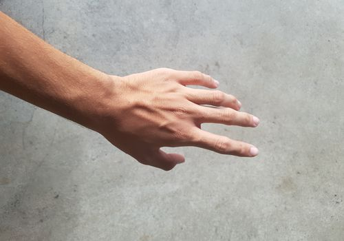 hand against grey cement wall