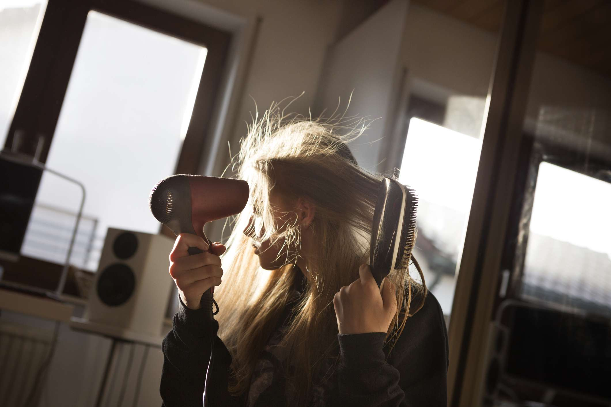 A blonde woman uses a blow dryer to dry her hair in the summer.