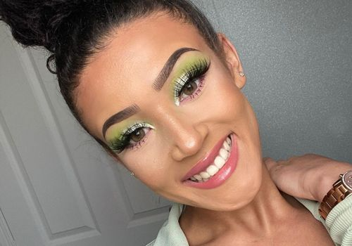 Woman smiling with green eyeshadow and hair in a bun