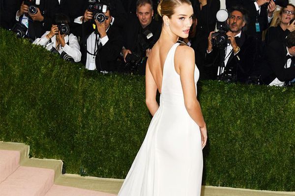 Rosie Huntington-Whiteley on the red carpet wearing a long, white dress