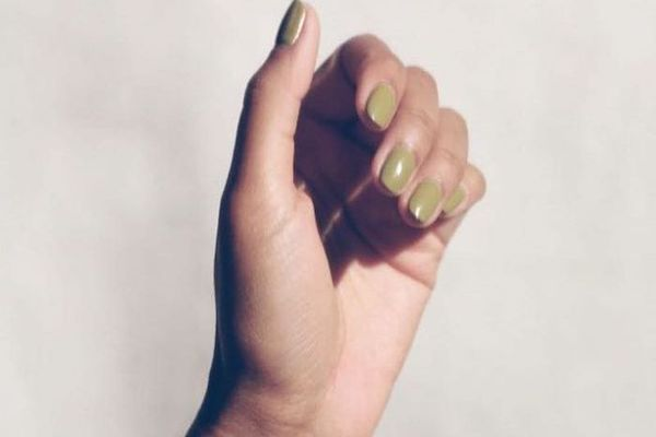 Hand with green nail polish