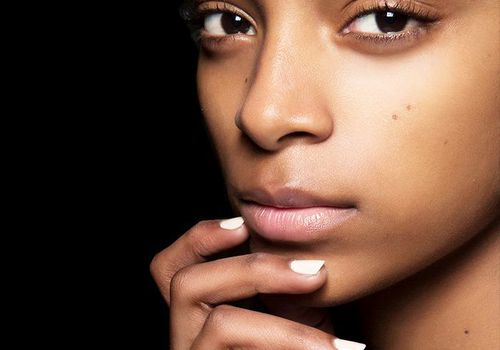young woman with no makeup and white nailpolish over a black background