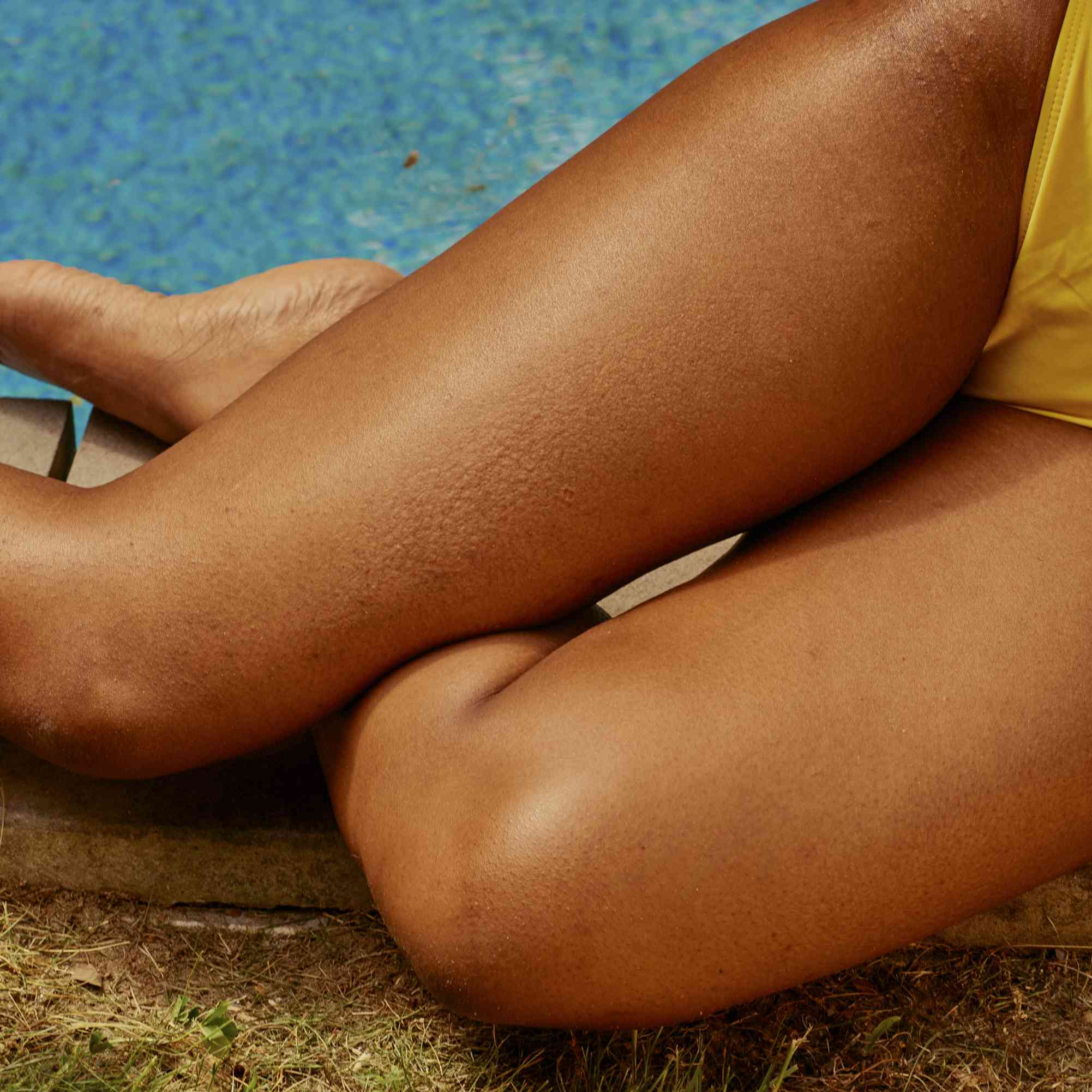 Person with tan, hair-free legs sitting by a pool