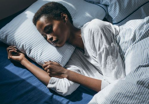 Woman sleeping on blue and white striped bedding.