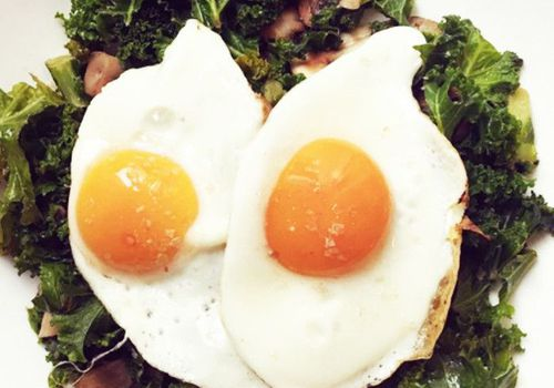 plate of sunny side up eggs atop a bed of greens
