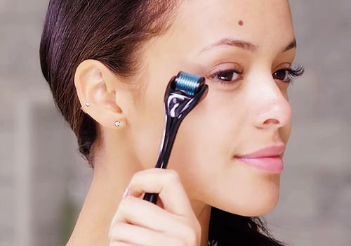 woman using dermaroller on face