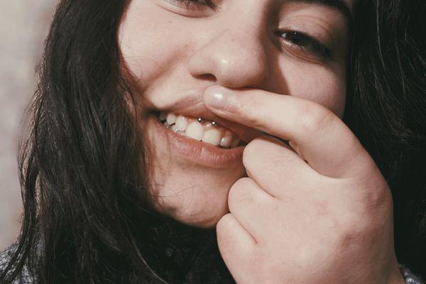 woman showing off inner lip piercing