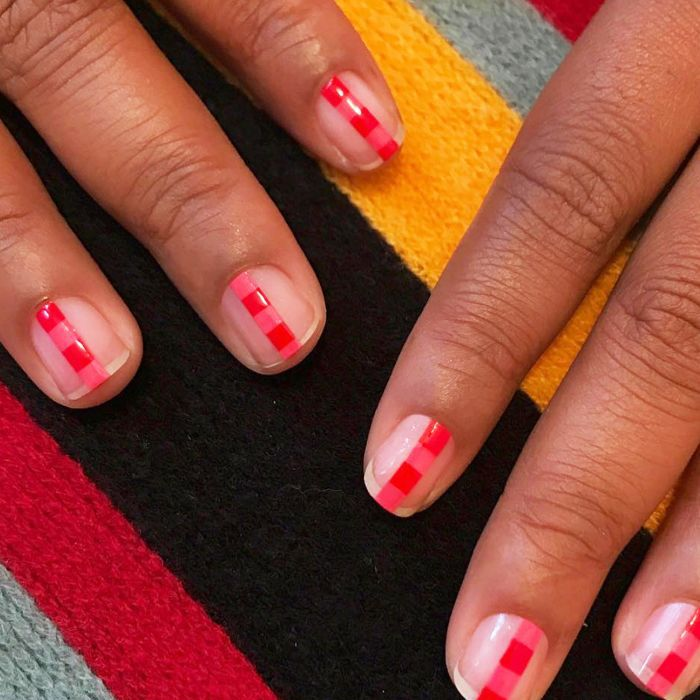 Two hands with red stripe manicure