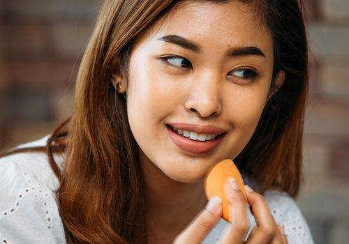 Asian woman applying foundation with a sponge
