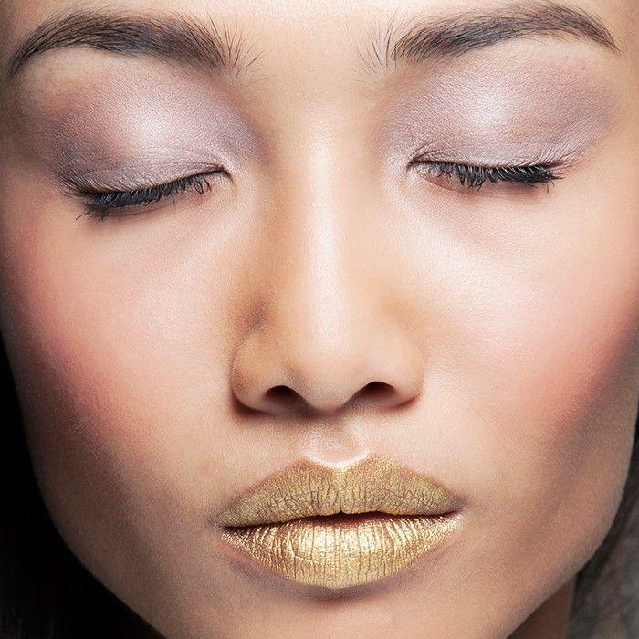 Woman wearing sheer purple eye shadow and gold lipstick