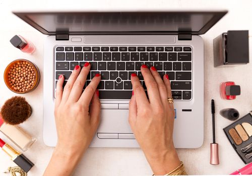 woman working on laptop computer with beauty products around
