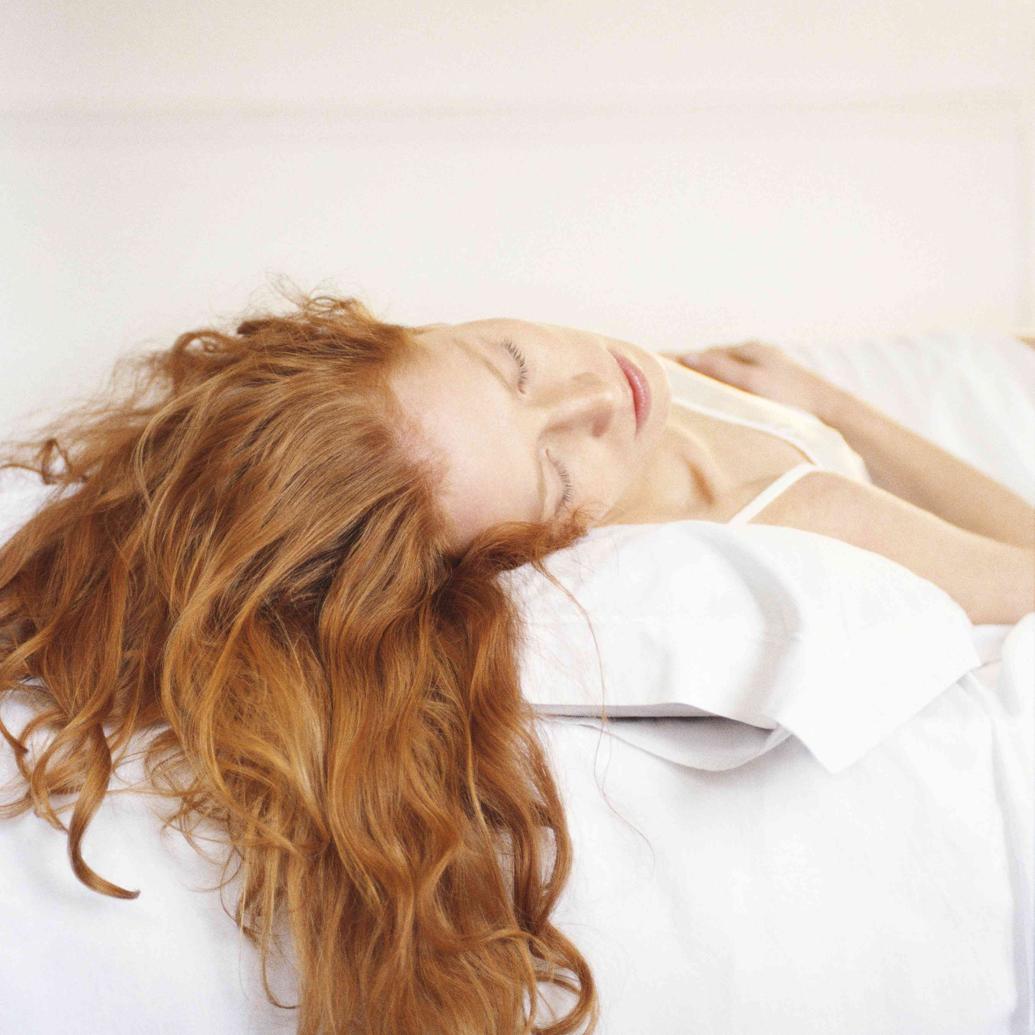 redheaded woman lying on a bed