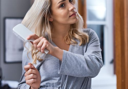 blonde woman brushing hair