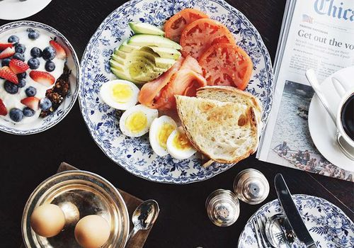 Breakfast foods, coffee, and a newspaper on a black table