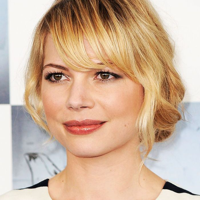 Michelle Williams on a red carpet with bangs and a low bun