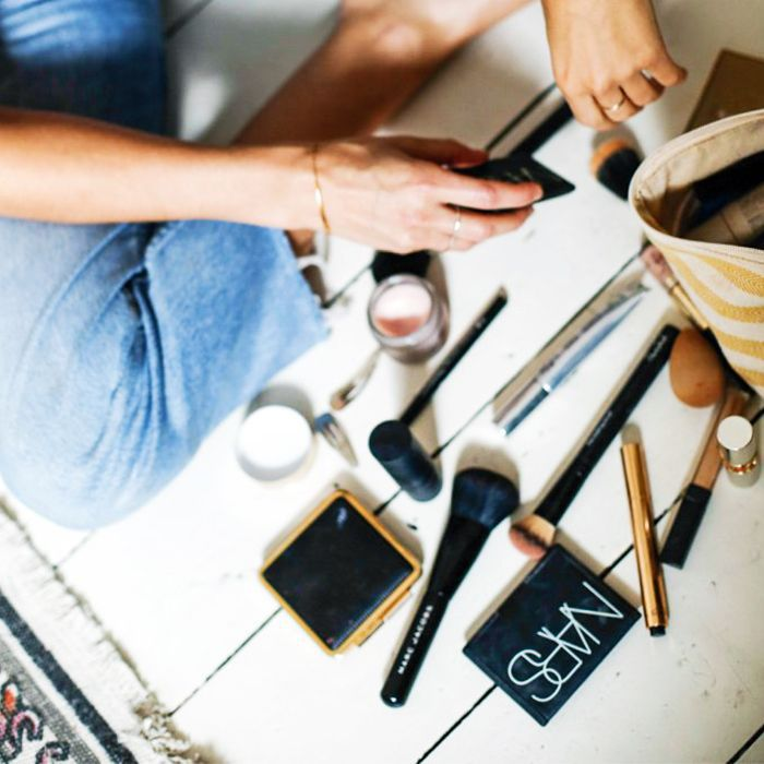 Blogger Lucy Williams sitting on floor with makeup products