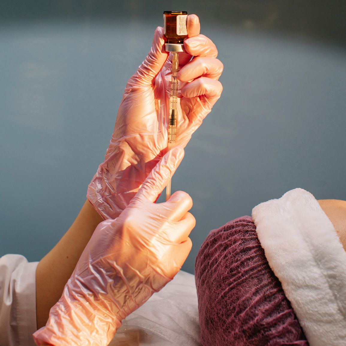 A woman holds a syringe and vial.