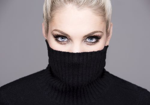 woman with a black turtleneck covering her face