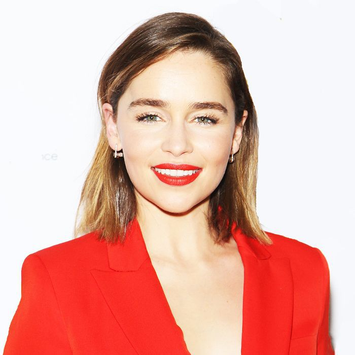 Emilia Clarke wearing red lipstick and red outfit