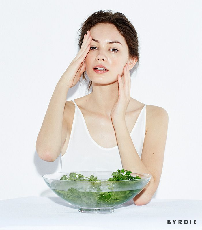 model with bowl of herbs in water touching face with both hands