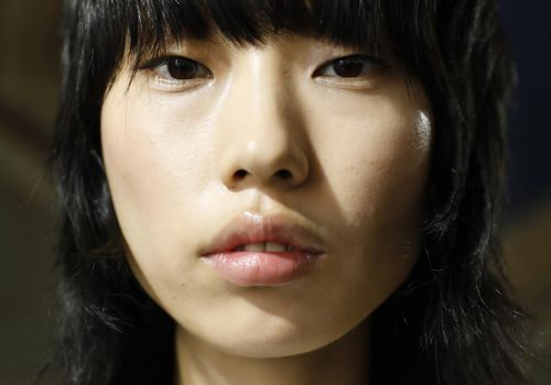 a model at fashion week with a short haircut with bangs