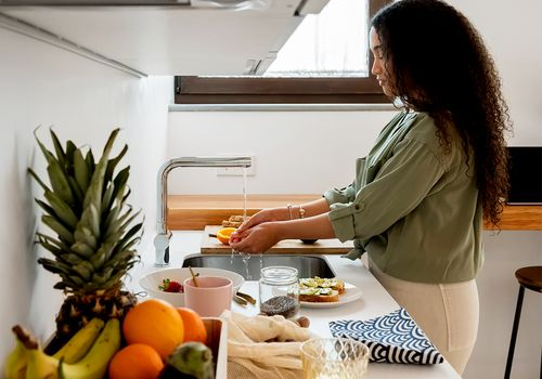 person cooking food in bright kitchen