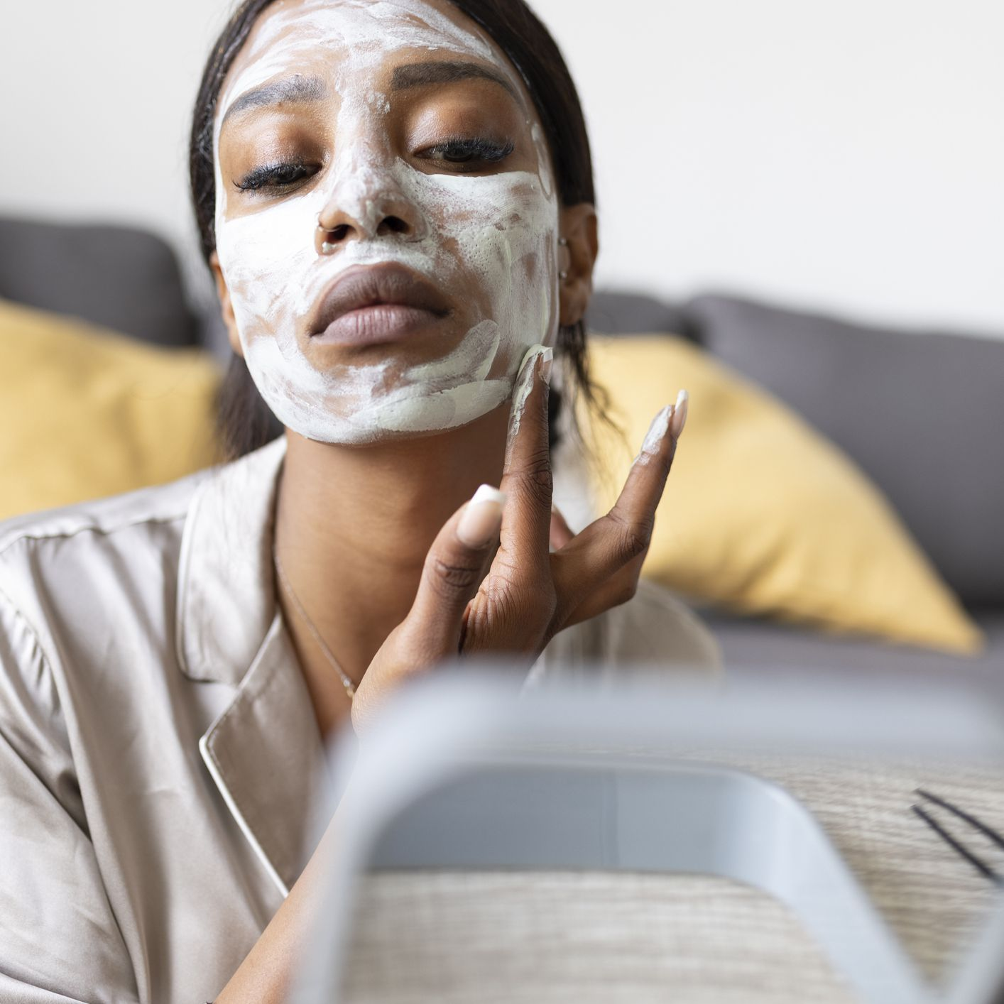 Woman applying face mask in front of mirror