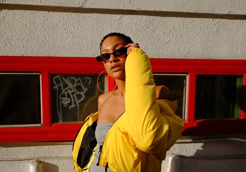 woman in yellow jacket wearing sunglasses