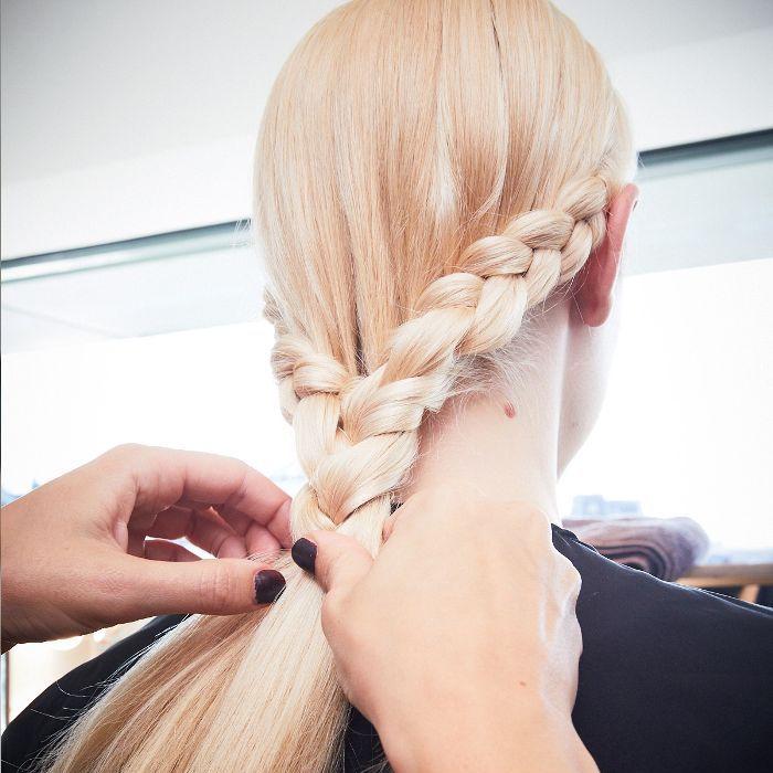 Model having her blonde hair braided backstage